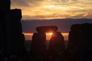 The sun rises behind Stonehenge.