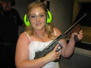This July 28, 2012 photo provided by Bob MacDuff shows Lindsae MacDuff holding an automatic weapon at the Gun store in Las Vegas after her shotgun wedding.