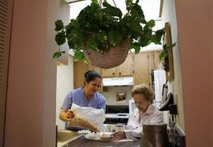 In this photo taken Friday, Sept. 3, 2010, home health aide Maria Fernandez, left, pours cereal for Herminia Vega, 83, right, as she performs household chores for Vega and her husband.