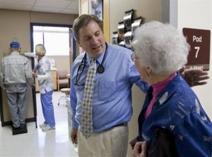 In this Oct. 26, 2009 file photo, primary care physician Dr. Don Klitgaard greets Muriel Bacon as her husband weighs in with a nurse, at the Myrtue Medical Center in Harlan, Iowa.