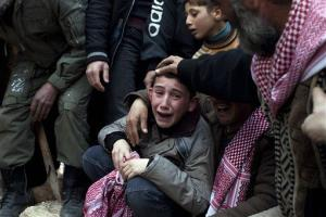 In this March 8, 2012 file photo, Ahmed, center, mourns his father Abdulaziz Abu Ahmed Khrer, who was killed by a Syrian Army sniper, during his funeral in Idlib, north Syria.