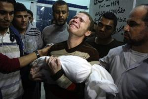 In this Nov. 14, 2012 file photo, Jihad Masharawi weeps while he holds the body of his 11-month old son Ahmad, at Shifa hospital following an Israeli air strike on their family house, in Gaza City.