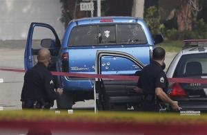This Feb. 7, 2013 file photo shows law enforcement officers looking over the scene of an officer involved shooting in Torrance, Calif.