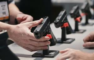 This Jan. 16, 2013 shows a Glock representative explaining features of the Glock 37 Gen 4 .45 caliber pistol at the 35th annual SHOT Show, in Las Vegas.