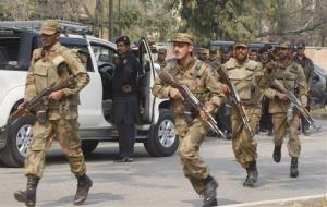 Pakistan army soldiers rush to the scene of a bombing in Peshawar, Pakistan on Monday, Feb. 18, 2013.