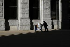 A US Postal Service employee pushes a cart full of mail through a patch of sunlight outside of an office building in Baltimore, Thursday, March 7, 2013.