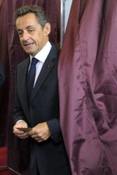 French former President Nicolas Sarkozy leaves the polling booth prior to cats his vote in the first round of French legislative elections in Paris, France, Sunday, June 10, 2012.