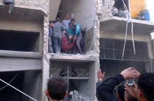Syrian citizens carry an injured man from a damaged building that was hit by a Syrian forces airstrike on the al-Marjeh neighborhood, of Aleppo, Syria, Tuesday March 19, 2013.
