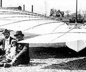 Gustave Whitehead and his 1901 monoplane. His infant daughter, Rose, sits on her father's lap, and the engine that powers the front landing-gear wheels is on the ground in front of the others.