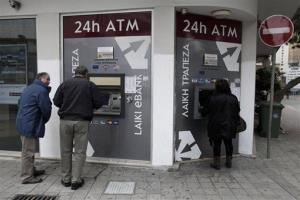 Cypriots use ATM machines outside of a closed bank in Nicosia, Cyprus.