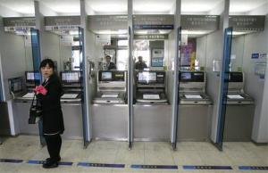 A customer stands in front of automated teller machines at a branch of Shinhan Bank after the bank's computer networks were paralyzed in Seoul, South Korea, today.