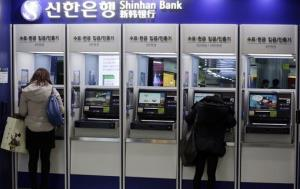 Customers use the automated teller machine at a branch of Shinhan Bank in Seoul, South Korea, earlier today.