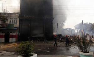 Burma firefighters walk around near a smoldering building as ethnic unrest between Buddhists and Muslims continues, in Meikhtila, Mandalay division, Burma, Friday, March. 22, 2013.