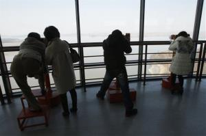 Visitors look at North Korea through binoculars at the Unification Observation Post in Paju near the demilitarized zone between the two Koreas, South Korea, Thursday, March 21, 2013.