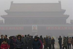 Visitors stand on Tiananmen Square across from a portrait of former Chinese leader Mao Zedong in thick haze in Beijing on Jan. 29, 2013.
