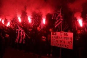 Supporters of the far-right party Golden Dawn hold up flares and a sign that reads in Greek ''No to the anti-Greek policy of Germany'' during a protest in Athens on Friday, March 22, 2013.
