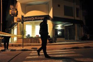 A private security officer, center, guards a branch of a Bank of Cyprus in the city of Limassol, Cyprus, early Monday.