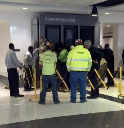 People lift up the sign that fell on a family, killing a child and injuring the mother and two other children, in the terminal at the Birmingham-Shuttlesworth International Airport.