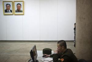 A North Korean soldier works at a computer terminal under portraits of late leaders Kim Il Sung and Kim Jong Il inside the Grand People's Study House in Pyongyang.