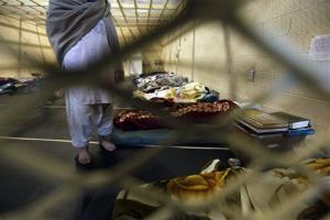 This March 23, 2011 file photo shows Afghan detainees through a wire mesh fence inside the Parwan detention facility near Bagram Air Field in Afghanistan.