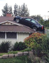 This photo released by the Glendale Police Department shows a black Cadillac that lost control and careened onto the roof of a neighbor's home on Saturday, March 23, 2013 in Glendale, Calif.