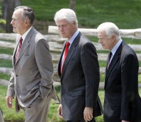 Former Presidents George HW Bush,,left,  Bill Clinton,center, and Jimmy Carter walk to the stage during a dedication ceremony for the Billy Graham Library.