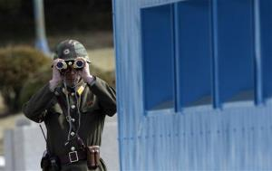 A North Korean soldier looks at the southern side at the border village of the Panmunjom (DMZ) that separates the two Koreas, in Paju, north of Seoul, South Korea, Tuesday, March 19, 2013.