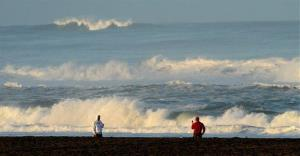 With a tsunami warning in effect for Northern California, two men watch the waves at San Francisco's Ocean Beach on Friday, March 11, 2011.