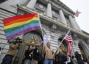 Billy Bradford of Castro Valley, Calif., waves a pair of flags outside San Francisco City Hall while same-sex couple line up to see if they can be married in San Francisco, Thursday, August 12, 2010.
