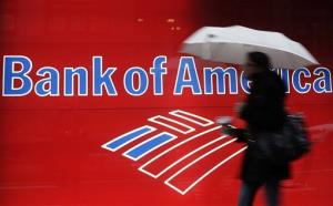 In this Dec. 7, 2011 file photo, a woman passes a Bank of America office branch, in New York.