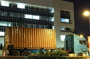 An armed police officer guards several trucks carrying containers after arriving at the country's Central Bank in Nicosia, Cyprus, on Wednesday, March 27, 2013.