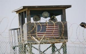 In this  May 13, 2008 file photo reviewed by the US Military, a  soldier looks through binoculars while standing on a guard tower at Camp 4 in the Guantanamo Bay US Naval Base in Cuba.