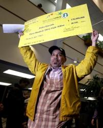 Pedro Quezada, the winner of the Powerball jackpot, holds up a promotional check during a news conference at the New Jersey Lottery headquarters, Tuesday, March 26, 2013, in Lawrenceville, NJ.