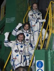 Russian Flight Engineer Alexander Misurkin, top, NASA Flight Engineer Chris Cassidy, and Soyuz Commander Pavel Vinogradov, bottom, wave farewell.
