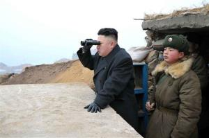 In this March 7, 2013, photo, North Korean leader Kim Jong Un uses a pair of binoculars to look at the South's territory.