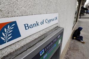 A beggar sits outside a Bank Of Cyprus UK branch in central London.