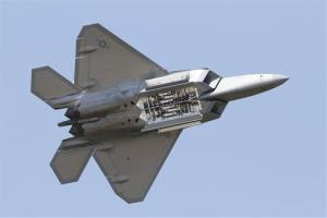 An Air Force F-22 Raptor displays its weapons bays as it goes through maneuvers.