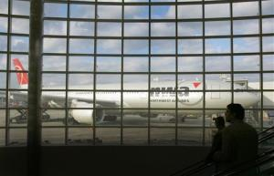 Travelers on a concourse escalator pass by a window and a Northwest Airlines jet beyond at the Detroit Metro Airport in Detroit, Mich.