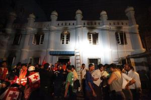 Red Cross workers and local Muslims gather outside a mosque after a fire broke out in Rangoon, Burma today.