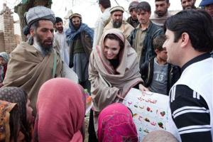 Angelina Jolie presents education materials to local Headteacher, Gul Rahman, left, and young schoolgirls in Qala Gudar village, Qarabagh District, outside Kabul, Afghanistan, on March 1, 2011.