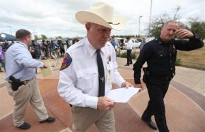 Kaufman County Sheriff David Byrnes, center, walks away after a news conference in Kaufman, Texas, on Sunday March 31, 2013.