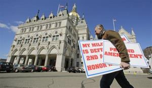 Jody Winslow, of Farmington, Conn., carries signs regarding the second amendment of the US Constitution as he heads back to the Capitol in Hartford, Conn., Wednesday, April 3, 2013.