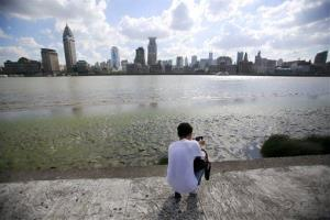A man photographs the bare riverbed of Huangpu River,  the result of lowered water level in Shanghai, China, on July 30, 2012.