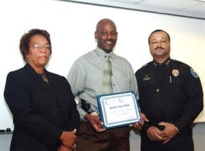 In this 2008 image provided by the Jackson, Miss. Police, Detective Eric Smith, center, flanked by Chief Rebecca Coleman, left, and Assistant Chief Lee Vance accepts a certificate of commendation.