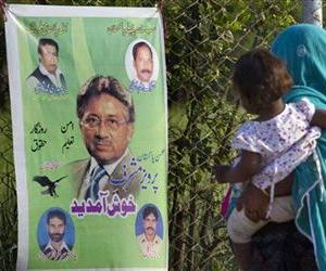 A Pakistani woman looks at a poster of former military ruler Gen. Pervez Musharraf along a roadside on the outskirts of Islamabad, Pakistan, April 7, 2013.