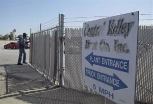 A security guard opens the gate at the Central Valley Meat Co., the California slaughterhouse shut down by federal regulators.