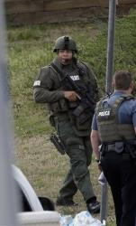A police officer holds a rifle as he walks near the hostage scene in Suwanee, Ga., Wednesday.