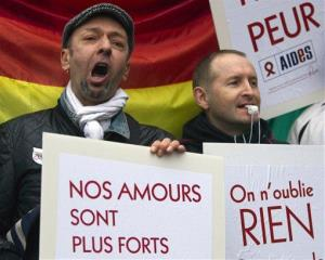 People demonstrate for equal rights with placards and flags in Paris, France, Wednesday, April 10, 2013.
