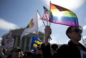 Kevin Coyne of Washington holds flags in front of the Supreme Court in Washington, Wednesday, March 27, 2013.