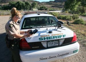 This undated photo provided by the Mesa County, Colo., Sheriff's Department shows a deputy getting ready to use a small drone equipped with a camera.